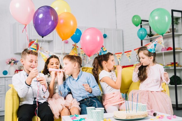group-children-sitting-sofa-holding-colorful-balloons-blowing-party-ho