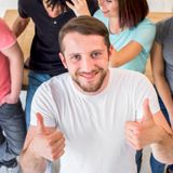 happy-young-man-standing-with-friends-showing-thumbup-gesture-looking-